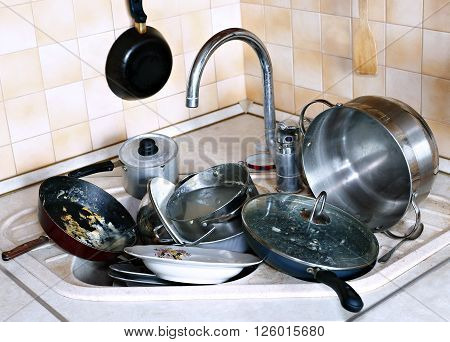 Many of dirty dishes in the sink in the kitchen