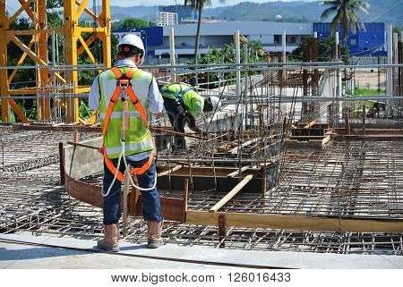 SELANGOR, MALAYSIA -FEBRUARY 13, 2015: Construction workers wearing safety harness belt, during working at height in the construction site area.
