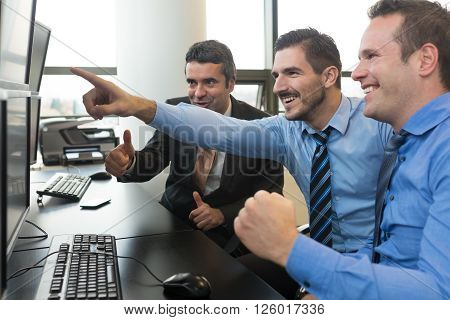 Successful business team. Stock traders looking at graphs, indexes and numbers on multiple computer screens. Colleagues in traders office. Business success.