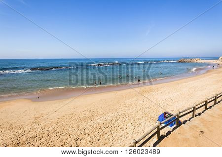 Beach ocean blue water rock tidal pool with holiday bathers swimming coastline landscape.