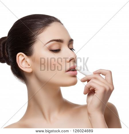 Beautiful young woman applying chapstick to lips. Isolated over white background. Copy space. Square composition.