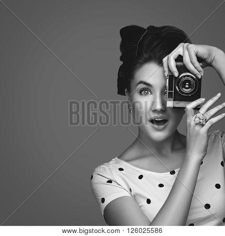 Beautiful young woman with retro photo camera. Surprised expression. Closeup portrait. Monocrome. Copy space. Square composition.