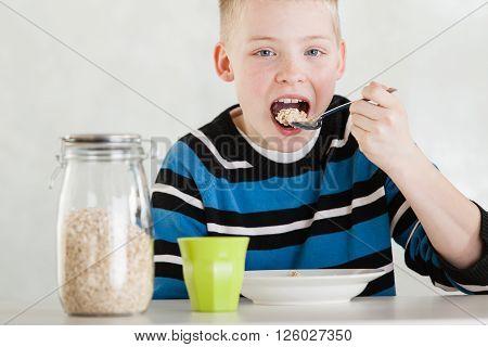 Single Child Feeding Himself Oatmeal