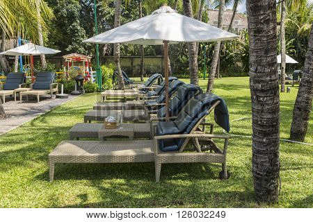 KUTA, BALI - MARCH 3, 2016: Kuta Beach palm coat luxury resort with swimming pool and sunbeds. Bali Indonesia.