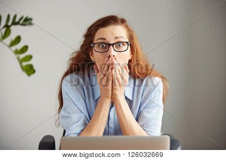 Portrait Of Young Shocked Businesswoman Covering Her Mouth In Surprise Sitting In Front Of The Lapto