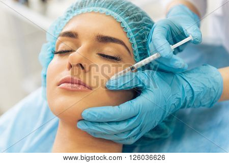 Beautiful young woman is getting an injection in her face lying with closed eyes