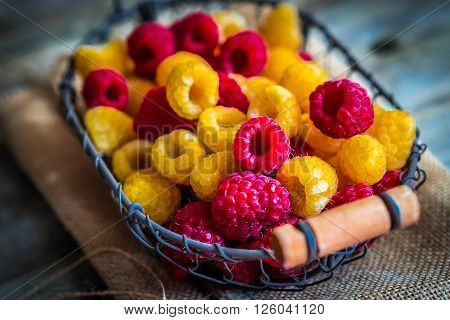 Image of Colorful raspberries on wooden background