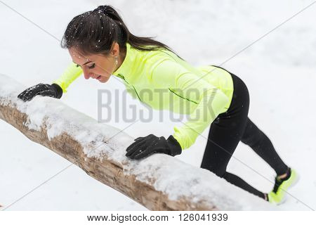 Fitness woman doing push ups Outdoor training workout winter forest