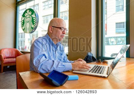 NEW YORK - CIRCA MARCH 2016: man in Starbucks Cafe. Starbucks Corporation is an American global coffee company and coffeehouse chain based in Seattle, Washington