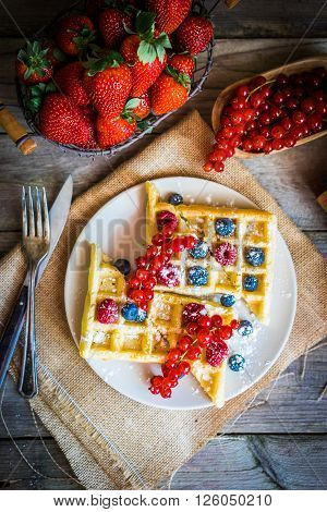 Image of waffles with berries on rustic background