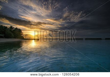 Beautiful ocean sunset with palm trees and blue water