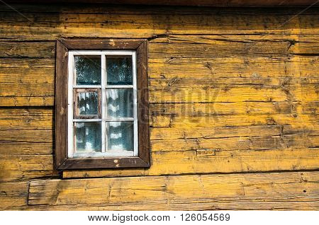 Yellow timbered wooden loghouse wall with window