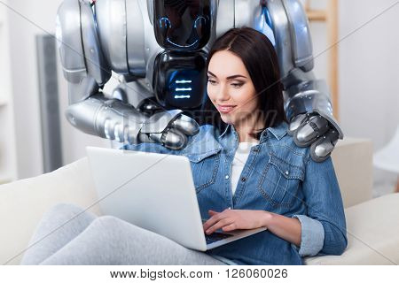 Just relax. Pleasant delighted positive girl sitting on  the couch and using laptop while modern robot massaging her shoulders