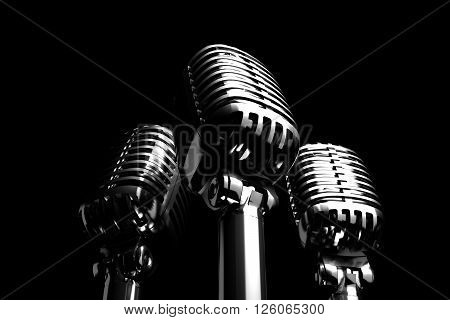 Three Silver retro microphones symbolizing trio, backing vocalist or a trio of singers. 3D Illustration.