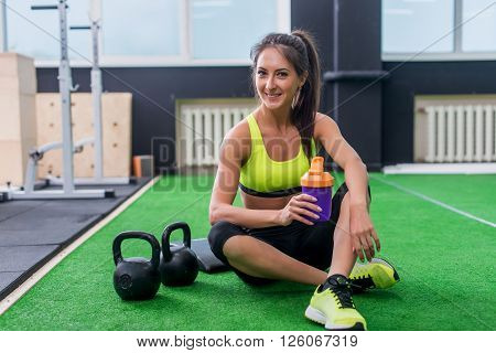 young sporty woman drinking water in gym, holding bottle,  having break. poster
