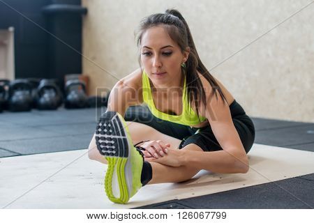 young woman stretching hamstring in gym, fit female doing warm-up on mat.
