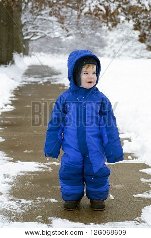 A caucasian toddler in a blue snowsuit stands on a sidewalk in winter while flurries fall