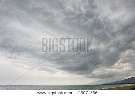 rainstorm, heavy overcast raiclouds over the sea beach