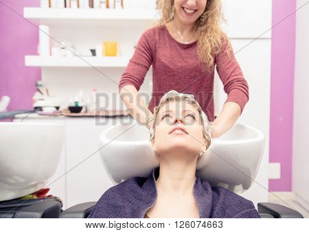 Woman make shampoo at the hair dresser - Hairstylist washing her customer's head in a spa salon