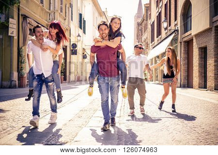 Young friends having fun outdoors - Six students outdoors men carrying two girls on piggyback