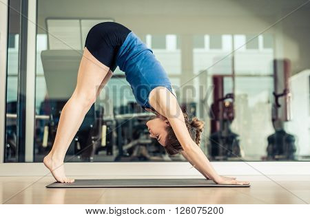 Portrait of a middle age woman in a yoga pose at the studio - Sportive girl training in a gym