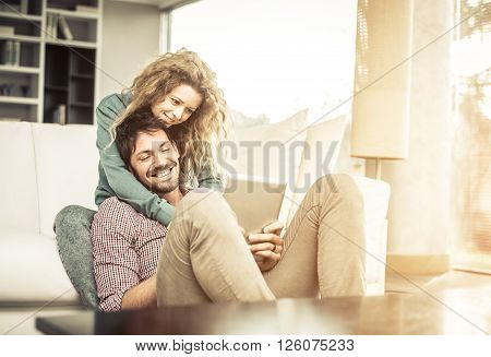 Couple of lovers at home watching the smartphone on the couch - Man and woman relaxing of the sofa woman leaning head on her boyfriend's shoulder