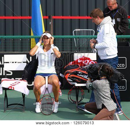 KYIV UKRAINE - APRIL 16 2016: Captain of Ukraine National Team Mikhail Filima (R) and player Lesia Tsurenko during BNP Paribas FedCup game Ukraine vs Argentina at Campa Bucha Tennis Club in Kyiv