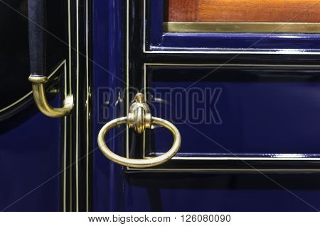 Car handle of vintage vehicle door, retro design, detail of old comfortable automobile with dark blue metallic bodywork, selective focus