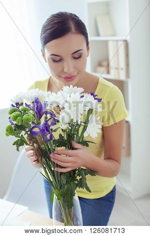 Pretty young woman is putting flowers in the vase. She is smelling them and smiling with pleasure. The lady is standing in her office