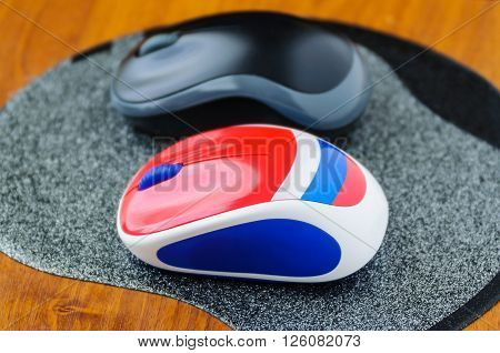 Two computer mouse on a gray mouse pad