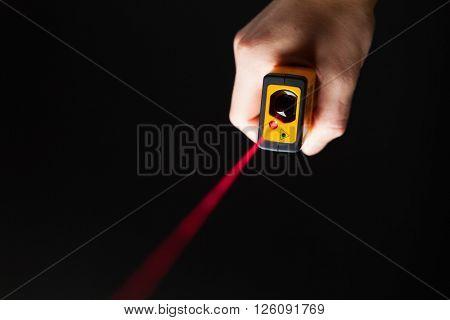 laser distance meter in hand, black background
