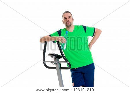 young man in green shirt with water bottle train with fitness machine