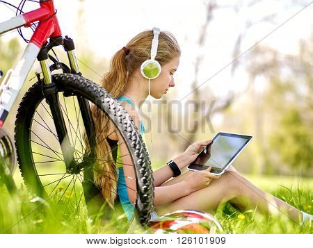 Bikes cycling girl wearing headset watch in pc tablet near bicycle.