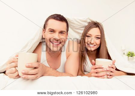 Smiling Man And Woman Basking With Blanket And Hot Tea