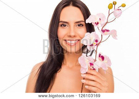 Portrait Of Smiling Pretty Woman Holding Orchid Near Her Face