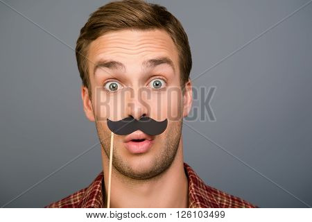 Close Up Portrait Of Surprised Funny Man Holding Paper Mustache