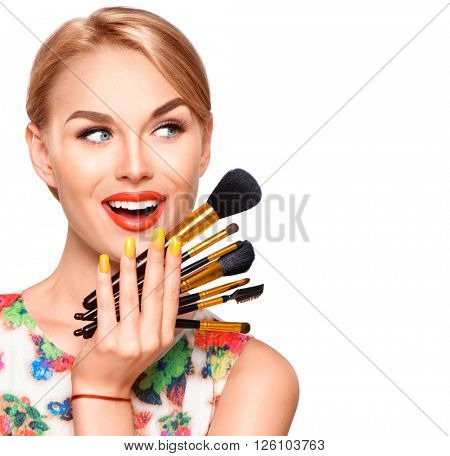 Beauty Woman with Makeup Brushes. Natural Make-up for Blonde Model Girl with Blue Eyes. Beautiful Face. Makeover. Perfect Skin. Applying Holiday Makeup with orange color lipstick and manicure