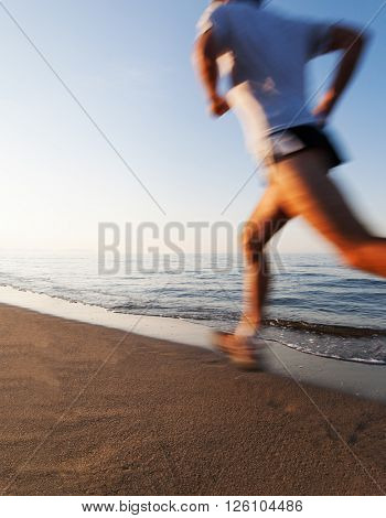 Young man running on a beach at sunrise. Motion blur effect. Concepts: well-being, vitality, healthy life, vacation, sport, training