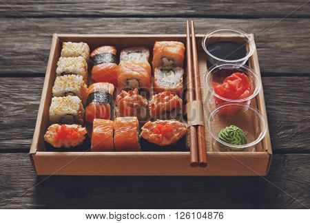 Japanese food restaurant, catering, sushi gunkan roll plate or platter set. Chopsticks, ginger, soy sauce, wasabi. Sushi at rustic wood background in take away, sushi set delivery box. Warm toning.