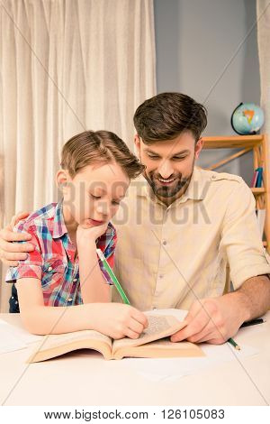 Little Boy Doing Hometask And Writing In Book With His Father