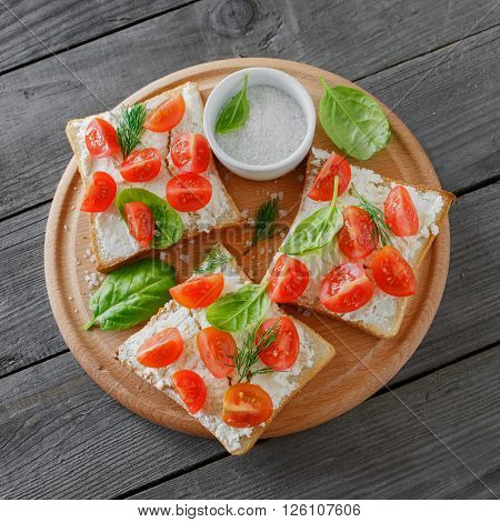 Tomato and cheese bruschetta on wooden cutting board on a wooden table top view with copy space. Healthy food. Square frame