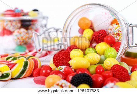 many different colorful candies sweetmeats and chewing gum scattered on the table on a white background with space for your text