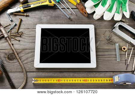 Tablet computer with a blank screen on a wooden table in the workshop with old tools top view
