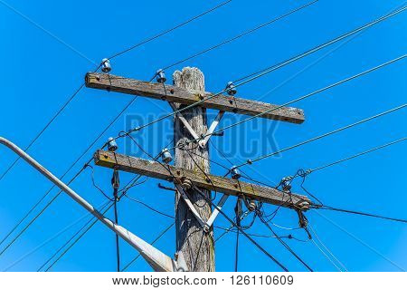 Old simple electricity rural wooden utility pole with cables and insulators against blue sky.