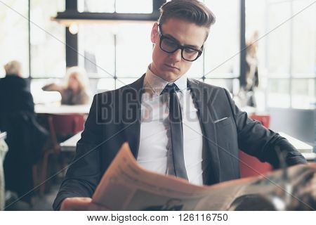 Man In Suit With Retro Glasses Reading Newspaper In Restaurant
