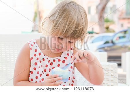 Cute Blond Caucasian Baby Girl Eats Frozen Yogurt