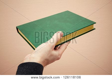 Book with empty dark green leather cover in male hand old style warm tonal correction photo filter effect