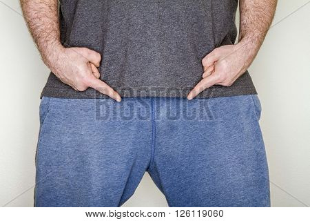 Man pointing to his genitals trying to show off what he has