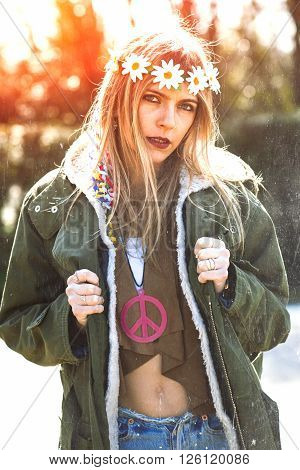 Girl hippie revolutionary in 1970 style with the symbol of peace and eskimo. Picture ruined simulation
