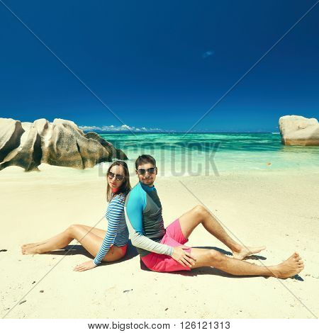 Couple on a tropical beach at Seychelles wearing rash guard poster
